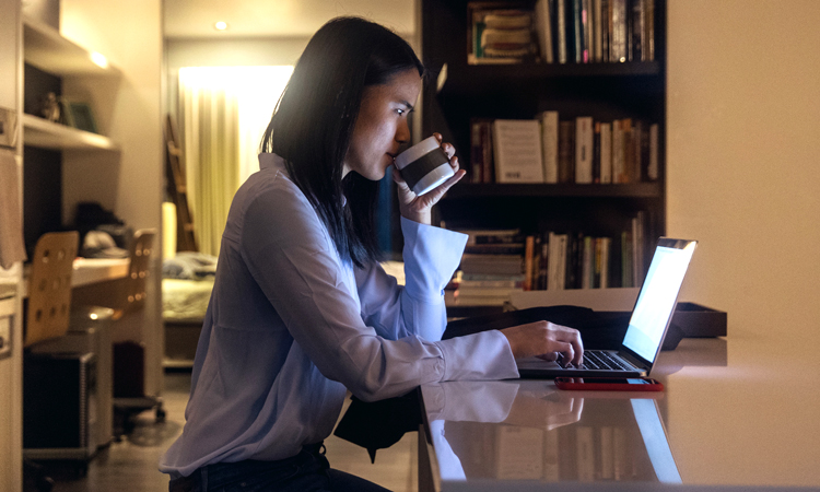Woman sitting at counter with a cup and a laptop